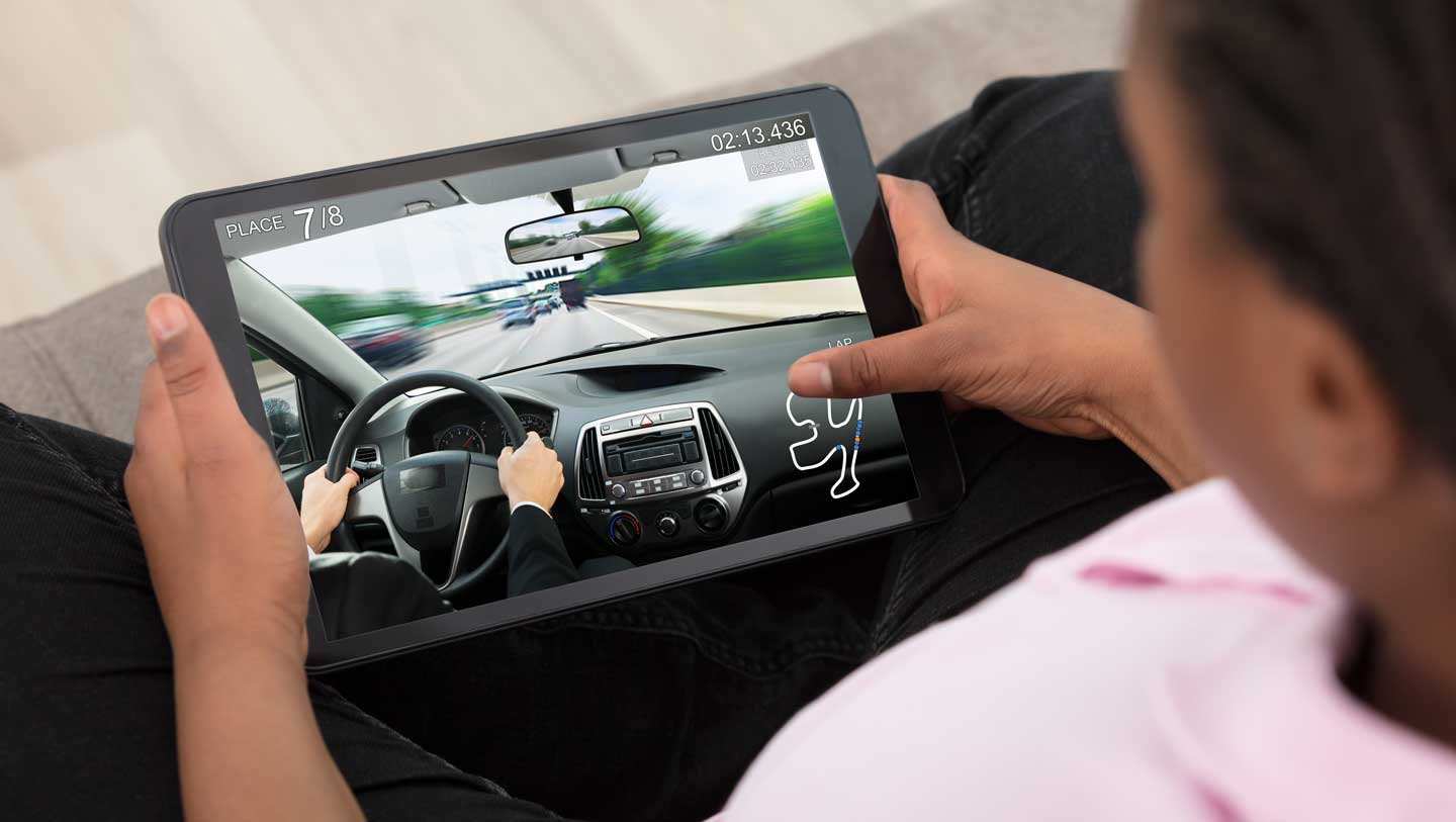 child plays driving game on tablet