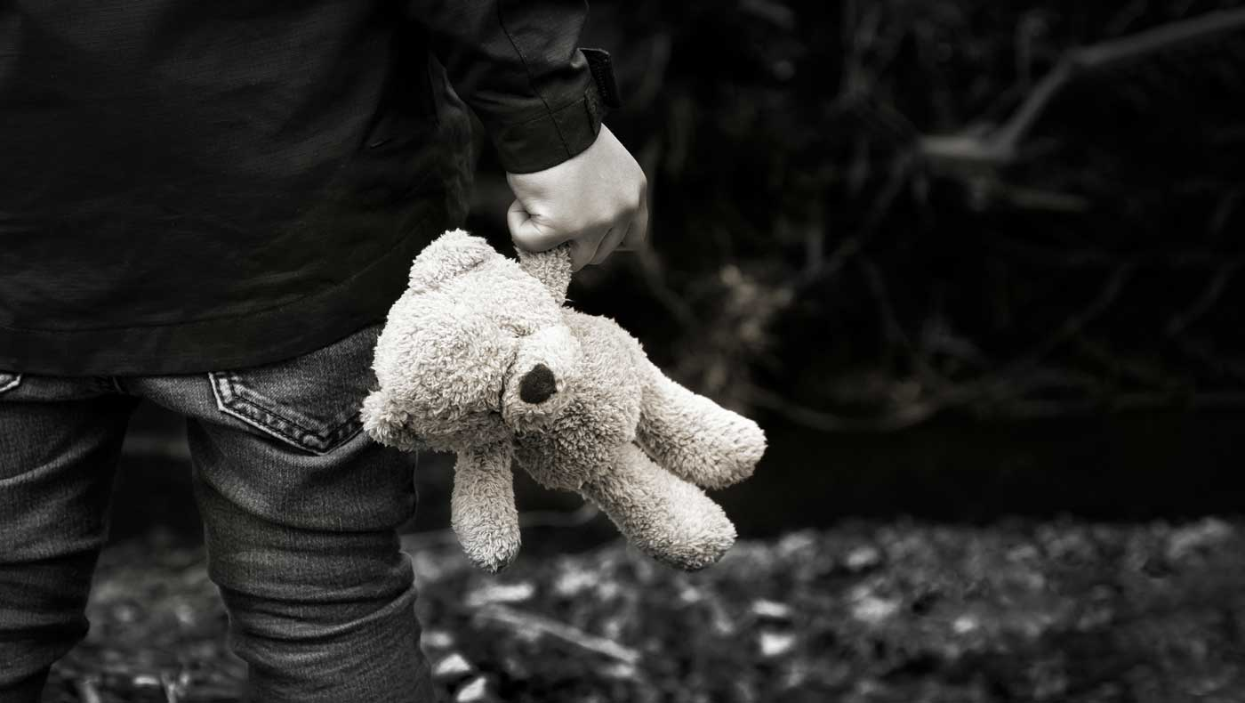 back view of child holding stuffed bear