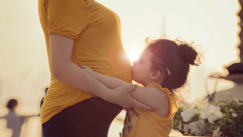 child kisses mom's pregnant belly