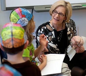 Sharon Ramey talks with children in paper brain hats