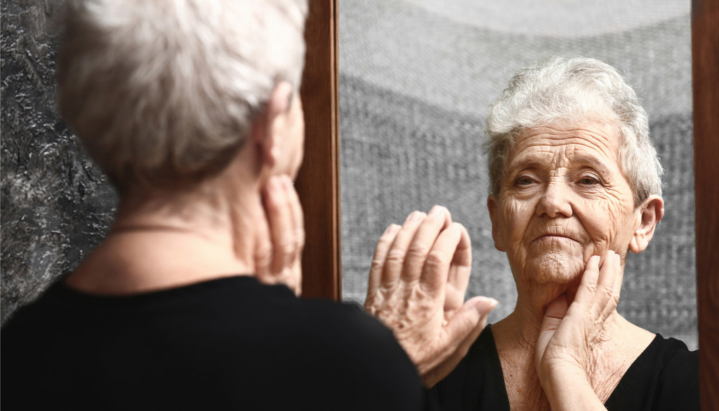 Older white woman looks into mirror