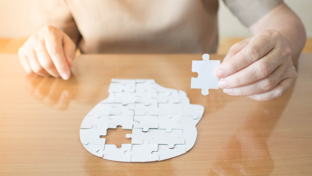 senior woman holding missing puzzle piece