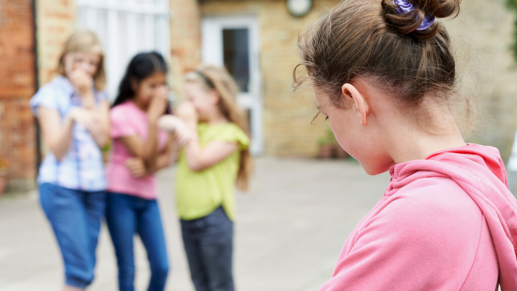 young girl looking back at girls talking behind her back