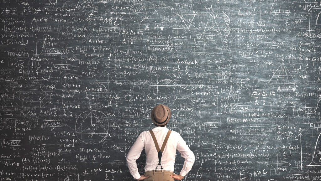 man standing in front of large chalkboard with math equations