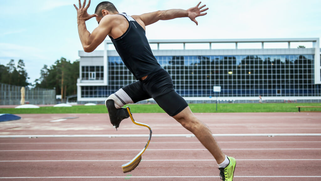 man with prosthetic leg running on a track